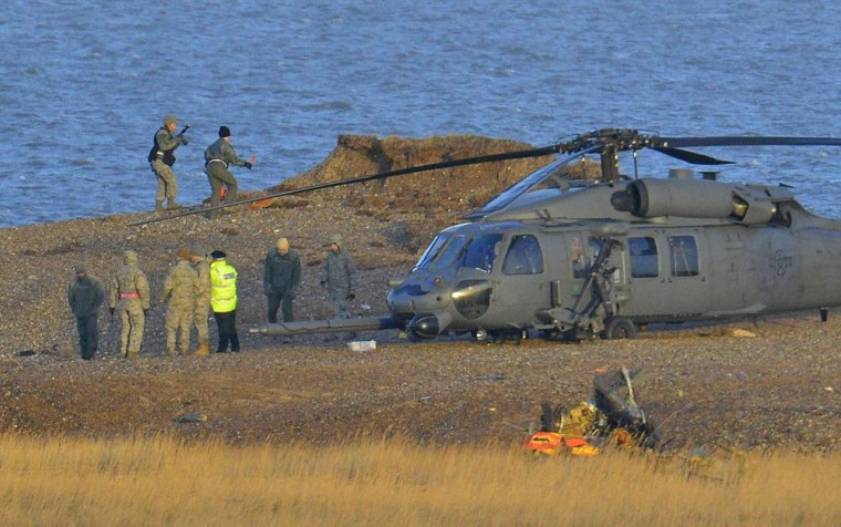 Image: A Pave Hawk helicopter, military personnel and emergency services attend the scene of a helicopter crash on the coast near the village of Cley in Norfolk, eastern England
