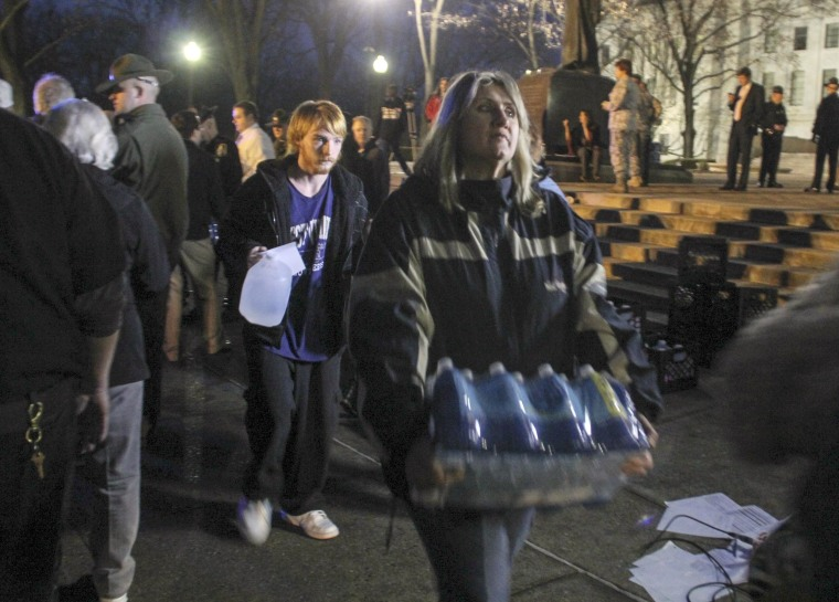 Image: Local residents pick up drinking water at the state capitol building in Charleston