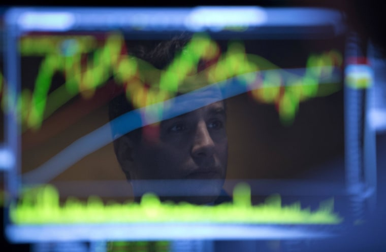 A New York Stock Exchange trader is reflected in a computer screen. But Wall Street's surge has not been matched by Main Street, where small businesses are only slowly recovering from the recession.