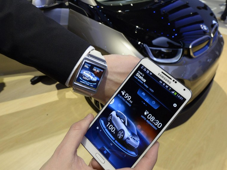 Image:  An exhibitor shows the Samsung smart watch and smart phone that interact with the BMW 3i electric car