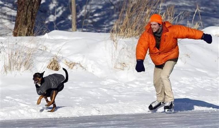 A man races his dog as he skates around Lake of the Isles in Minneapolis.
