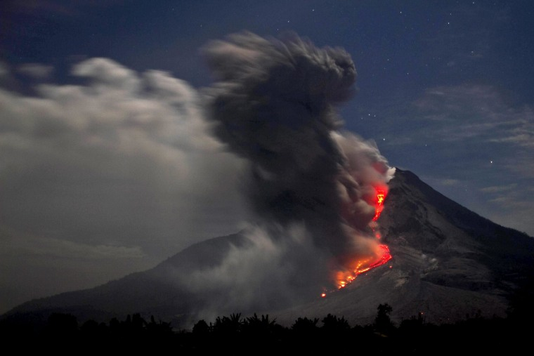epa04020864 Mount Sinabung spews hot lava and volcanic ash as it is seen from Karo, North Sumatra, Indonesia, 14 January 2014. Thousands of people have been sheltering for months in mosques, churches and government buildings just out of reach of the past months' eruptions of Indonesia's Mount Sinabung. The 2,460-metre volcano had been dormant for 400 years before it erupted in August 2010, forcing more than 30,000 to flee their homes.  EPA/ADE SINUHAJI