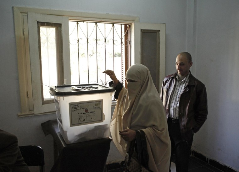 Image: A woman casts her vote at a polling booth on Wednesday in the rural district of Fayoum, Egypt.