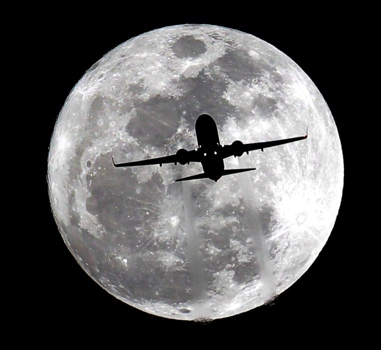 Image: A full moon backlights an airplane