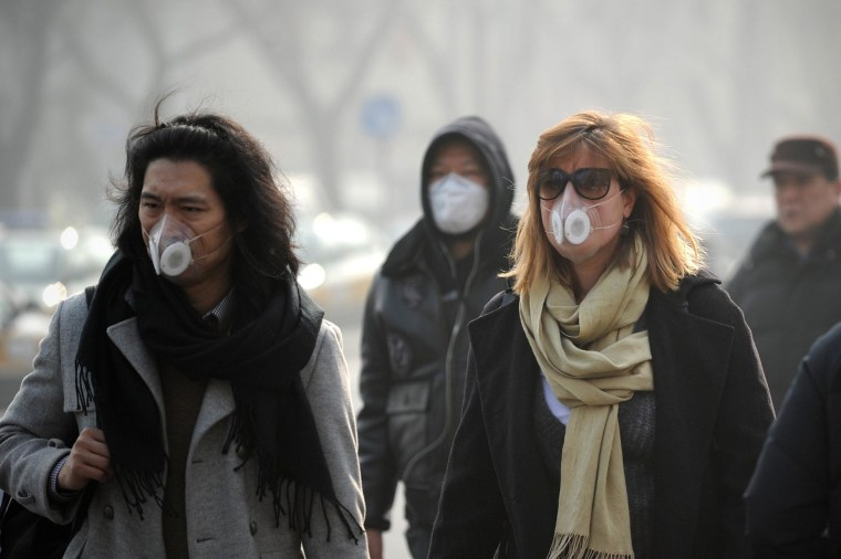 Image: People wearing face masks walk along a street in Beijing