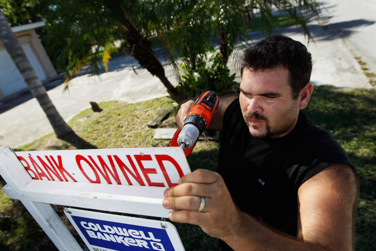 Renzo Salazar places a bank owned sign on a for-sale sign in Miami. The number of new home foreclosures fell last year to the lowest since 2006.