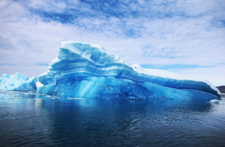 Image: Calved icebergs from the nearby Twin Glaciers float on the water in Greenland.