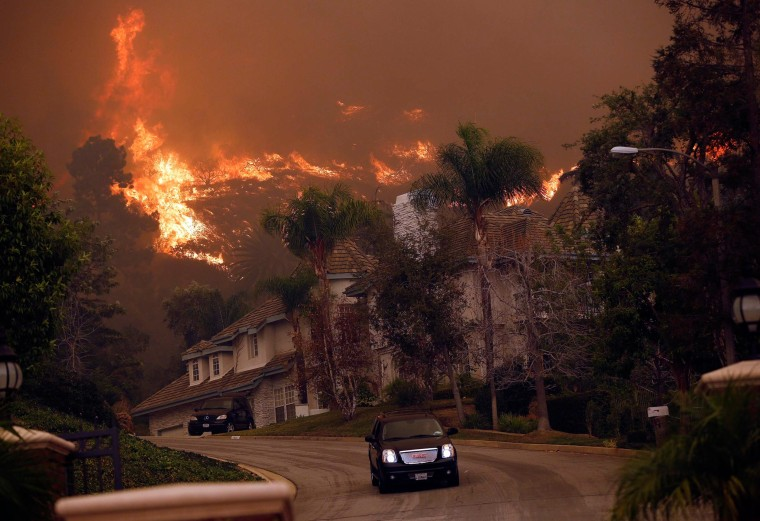 Image: A car drives away from the Colby Fire in hills above Glendora, Calif.