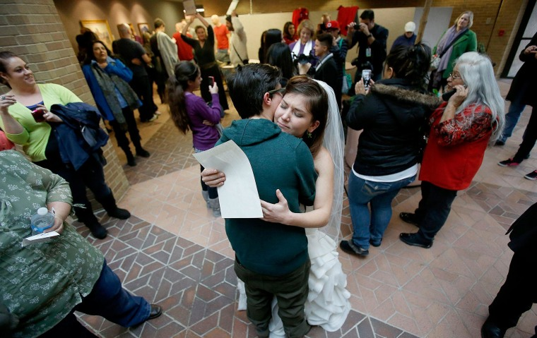 Image: A couple hugs after getting married at the Salt Lake County clerk's office Monday, Dec. 23, 2013.