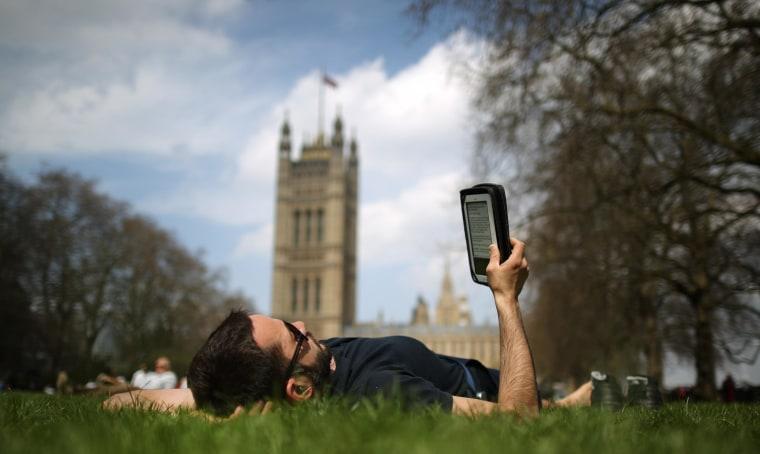 A man reads an e-book in London's Victoria Tower Gardens.