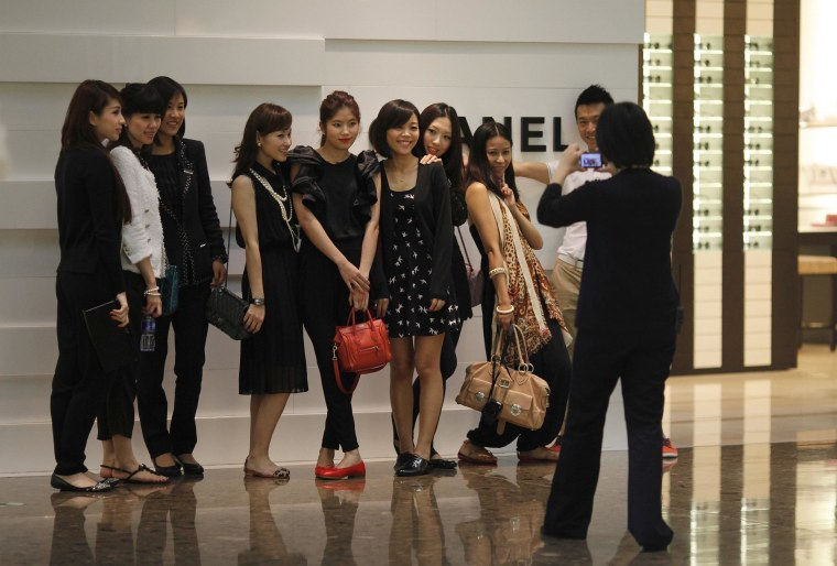 Shoppers pose for a picture in front of a Chanel luxury boutique at the IFC Mall in Shanghai.