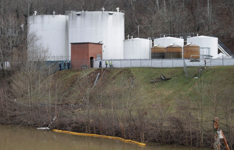IMAGE: Workers inspect an area around storage tanks where a chemical leaked into the Elk River.