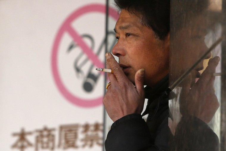 "Image: A man smokes in front of a ""no smoking"" sign outside a shopping mall in Shanghai"