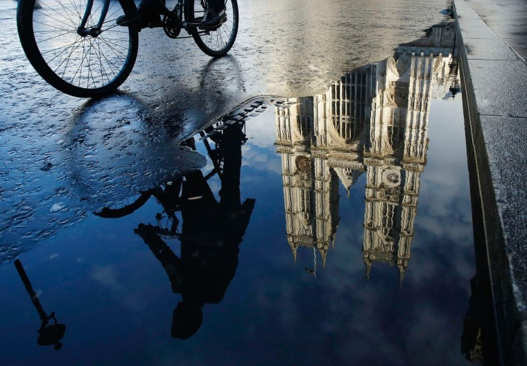 Image: A cyclist is reflected in a puddle as he passes Westminster Abbey in London