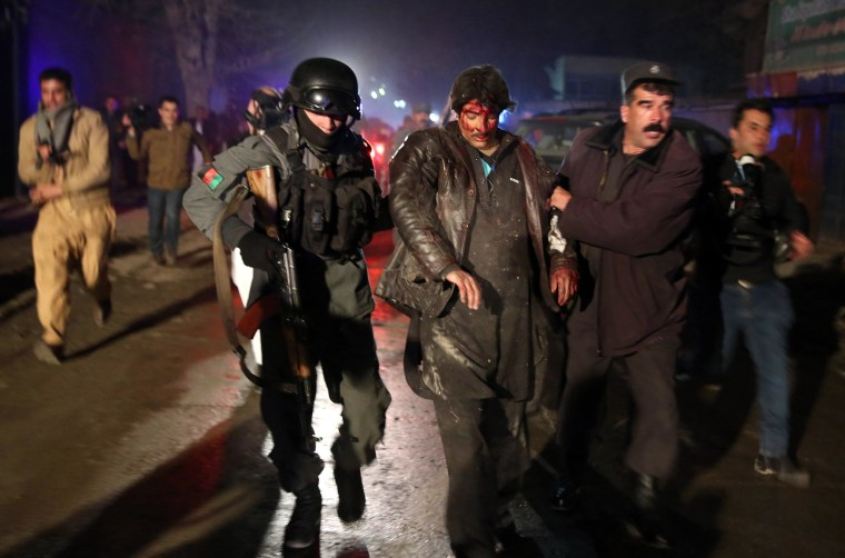 Image: Afghan police forces help an injured man after a bomb attack