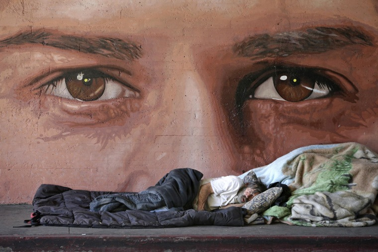 Image: A homeless man naps in front of a mural painted by artist Ruben Soto on Friday in Los Angeles.