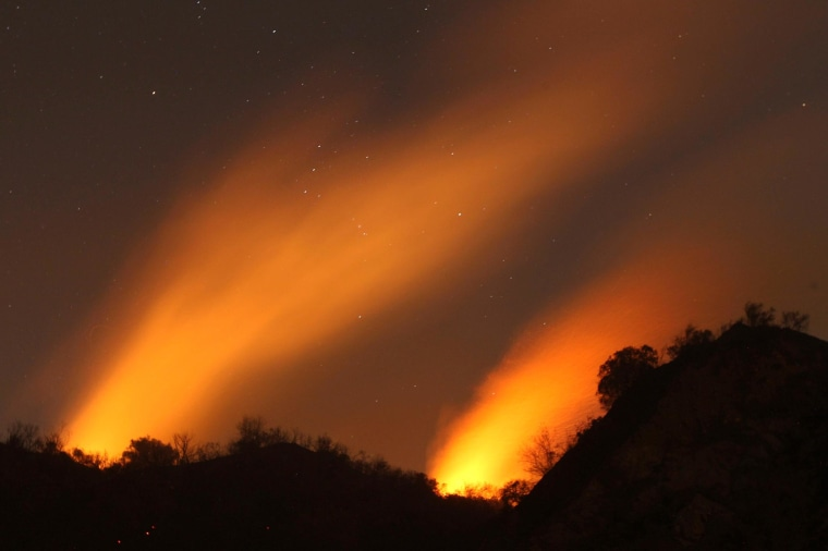 Image: Smoke rises under a starry sky at the Colby Fire in Glendora, Calif.