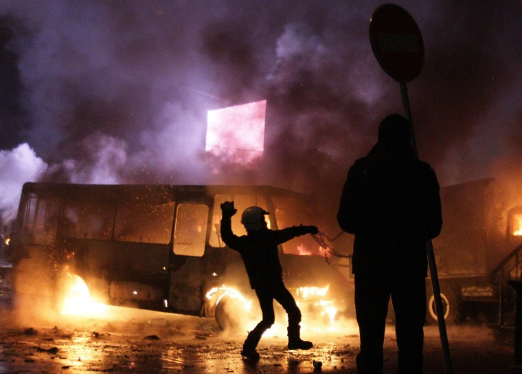 Image: Protesters clash with riot police next to a bus in flames in Kiev.