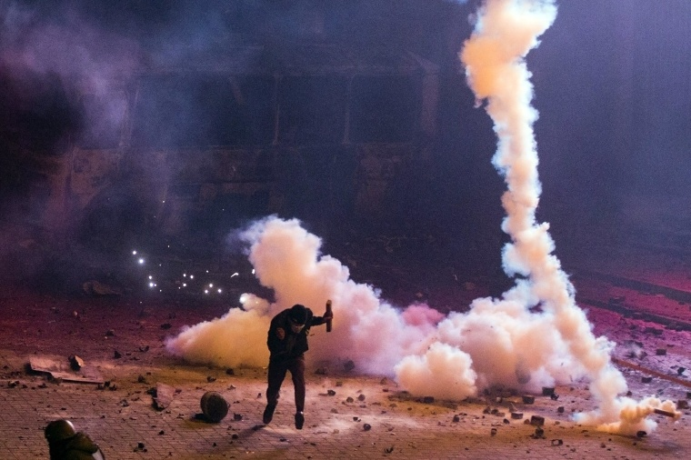Image: A protester runs during clashes with police in Kiev.