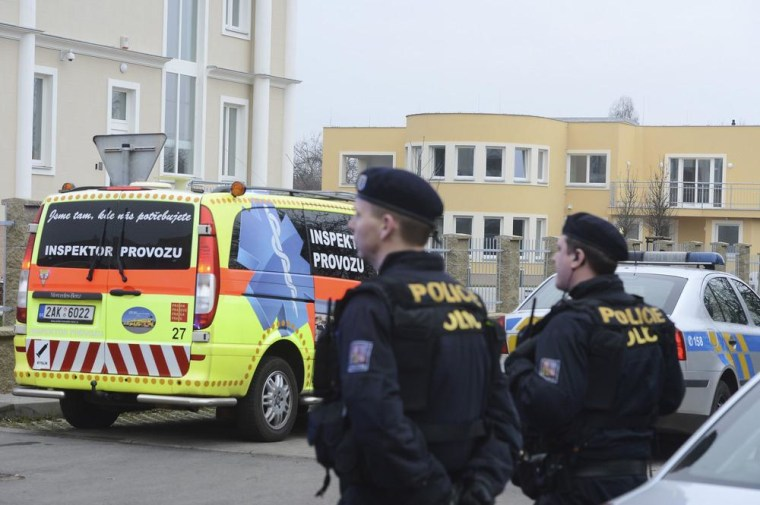 Image: Policemen observe the situation near the residence, right back, of Palestinian ambassador to the Czech Republic Jamal Al Jamal