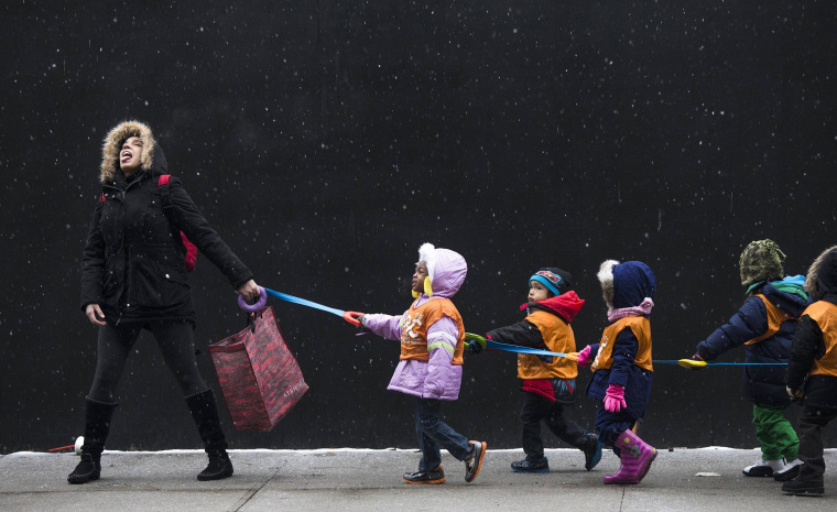 Image: A Harlem school teacher attempts to catch snowflakes while leading her students to a library, on Jan. 10 in New York City.