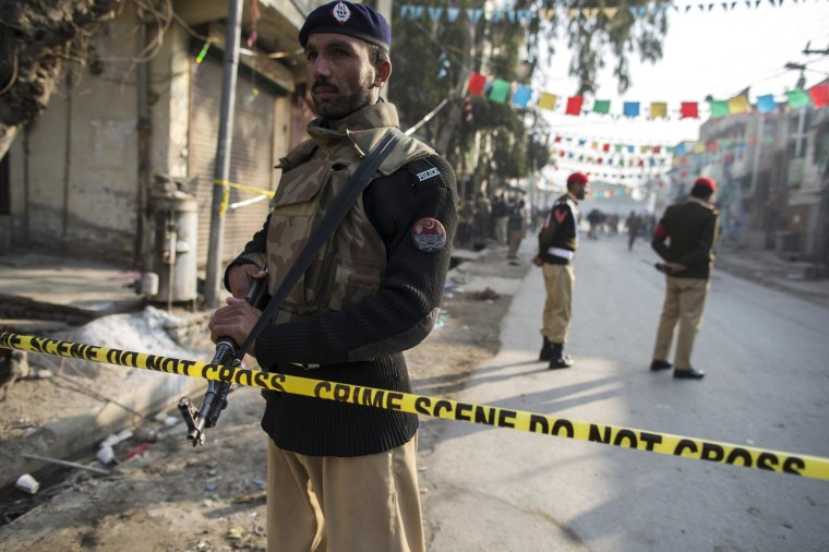 Image: A policeman cordons off the site of a suicide blast in Rawalpini