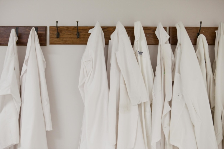 Lab coats hang in a row at a hospital. New guidance suggests that doctors and other health workers launder their coats at least once a week and hang them on hooks when they're actually examining patients.
