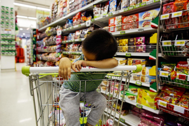 Image: A boy sleeps in a shopping cart at a department store in Bangkok.