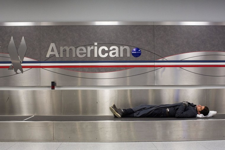 Image: A man sleeps on a conveyer belt under an American Airlines logo at John F. Kennedy International Airport in New York