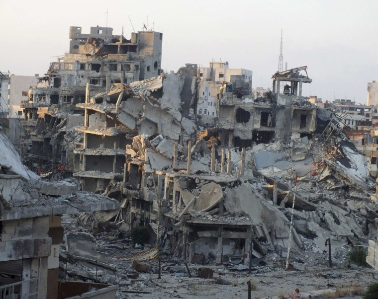 A general view shows damaged buildings on a deserted street in the besieged area of Homs July 13, 2013.