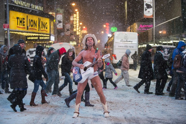 Image: Robert Burck, also known as the original 'Naked Cowboy', performs in a snow storm on the streets of Times Square, New York