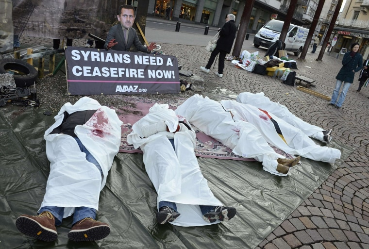 Image: Activists take part in a street performance Wednesday during a protest action calling for an immediate ceasefire and an end to the war in Syria, near the venue of the peace talks in Montreux, Switzerland.
