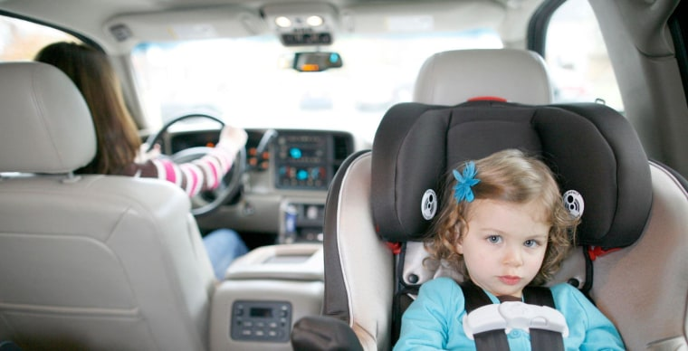 A child sits in a rear-facing car seat with an adult in the driver's seat.