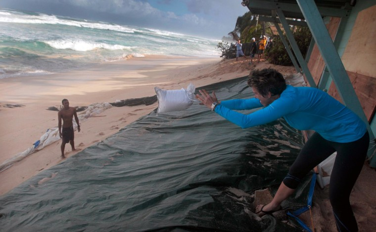 Image: Alice Lunt tosses a sandbag to a volunteer as high surf hits the north shore of Hawaii