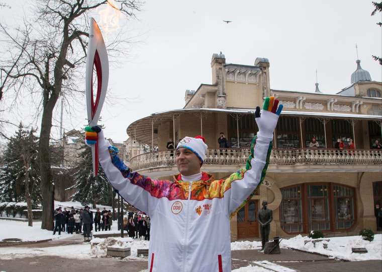 Torch bearer Andrei Yurgin poses Thursday with an Olympic torch during the torch relay in Pyatigorsk, a city in Russia's North Caucasus.