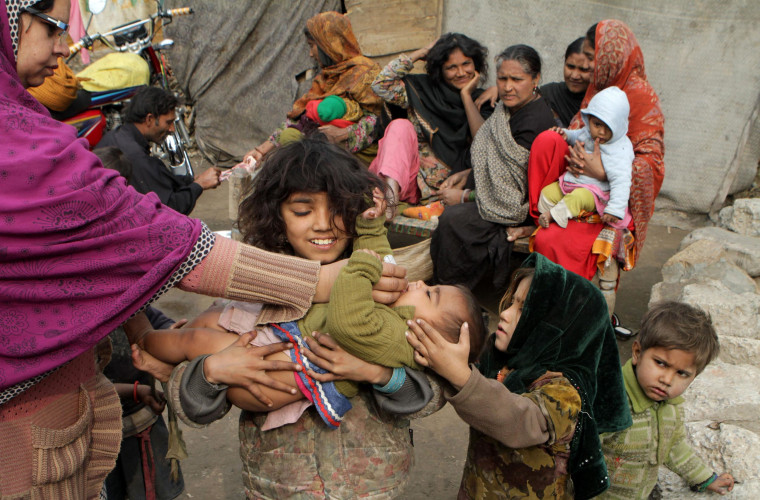 Image: A Pakistani health worker gives a polio vaccine to a child