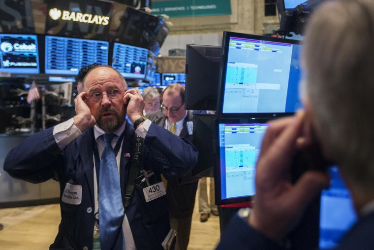 Traders work on the floor of the New York Stock Exchange on Thursday. The Dow ended the day 175 points lower on concerns over global growth.