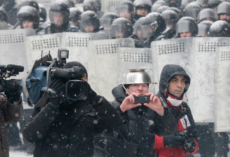 Image:  Reporters take pictures during clashes between protesters and police in central Kiev