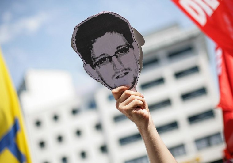 Image: A protester holds an image of NSA leaker Edwards Snowden.