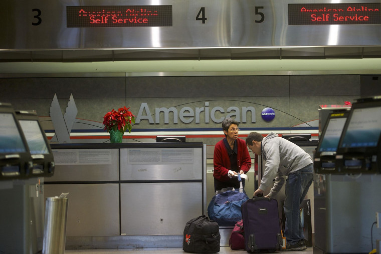 Image: A man checks luggage at the American Airlines check-in counter at Philadelphia International Airport