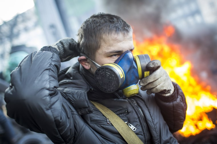 KIEV, UKRAINE - JANUARY 24: An anti-government protestor puts on a gas mask near Dynamo Stadium on January 24, 2014 in Kiev, Ukraine. Talks to resolve the political stalemate in the Ukraine have failed as anti government protests continue in the capital and opposition leader Vitali Klitschko urges the government to call a snap election. (Photo by Rob Stothard/Getty Images)