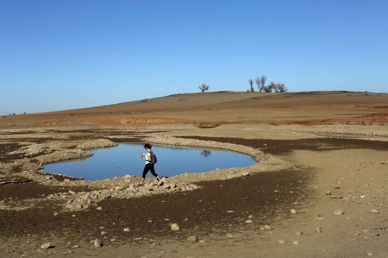 A visitor walks near the receding waters at Folsom Lake, which is 17 percent of its capacity, in Folsom, California January 22, 2014. California Governor Jerry Brown last week declared a drought emergency, and the dry year of 2013 has left fresh water reservoirs with a fraction of their normal water reserves. Picture taken January 22, 2014. REUTERS/Robert Galbraith (UNITED STATES - Tags: ENVIRONMENT TPX IMAGES OF THE DAY)