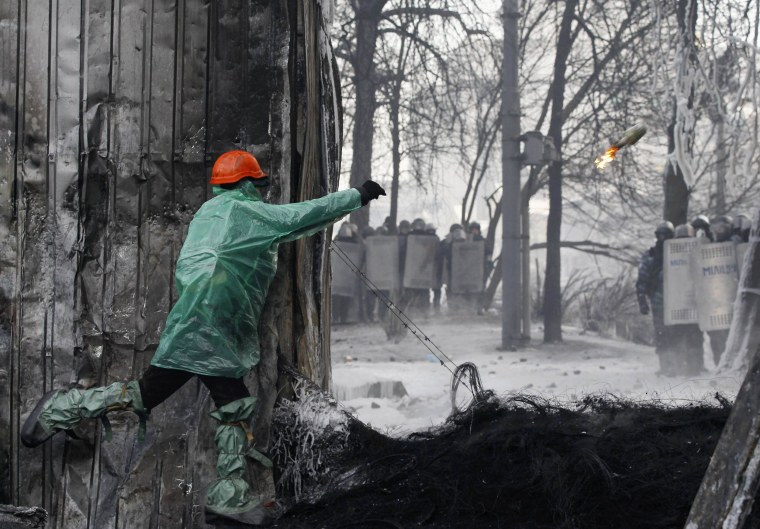 Image: An anti-government protester throws a Molotov cocktail towards riot police at the site of clashes in Kiev