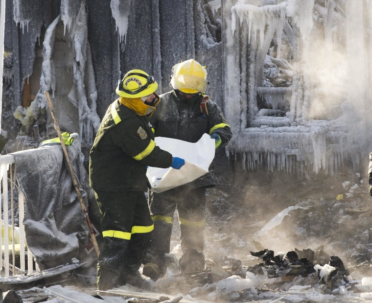 Image: Investigators remove evidence as they search through the icy rubble Friday of a fire that destroyed a senior residence in L'Isle-Verte, Quebec.