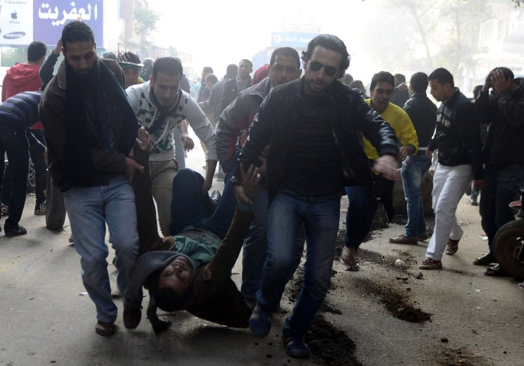 Supporters of the Muslim Brotherhood and ousted Egyptian President Mohammed Morsi carry an injured demonstrator who was shot during clashes in Cairo, Jan. 25, 2014.