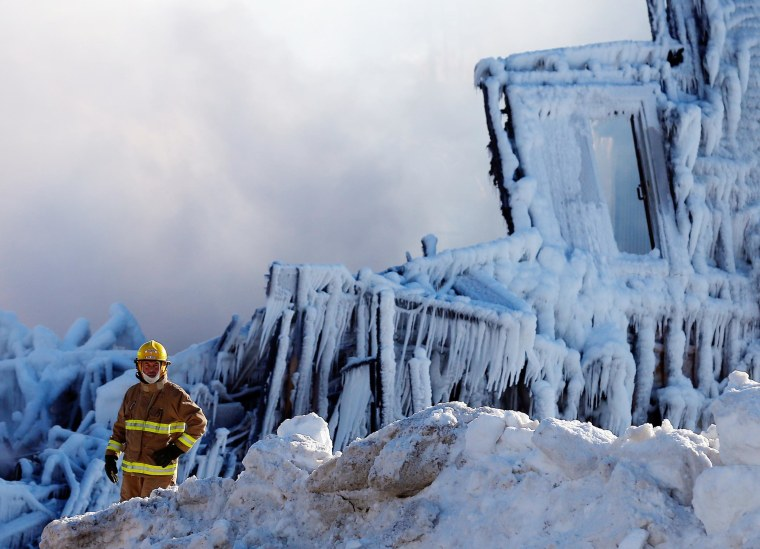 Image: A firefighter looks on at the seniors residence Residence du Havre after a fire in L'Isle Verte
