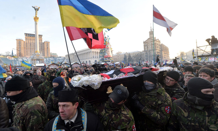 Image: Anti-government protesters carry the coffin of Mikhail Zhiznevsky during a funeral ceremony held on Kiev's Independence Square