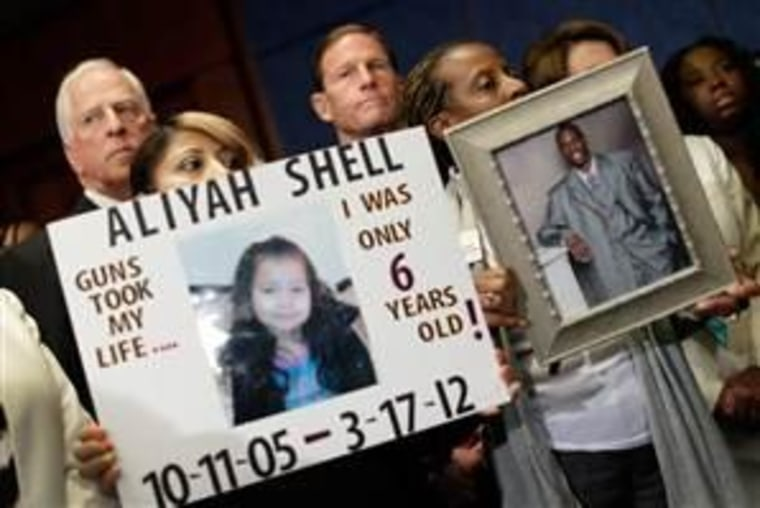 Diana Aguilar (L) and Tonya Burch (R) hold photos of their children during a press conference at the U.S. Capitol calling for gun reform legislation