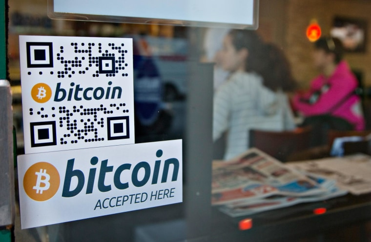 Signs on window advertise a bitcoin ATM machine that has been installed in a Waves Coffee House in Vancouver, British Columbia in this October 28, 2013 file photo.