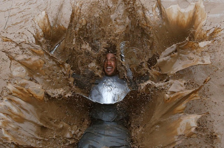 Image: Competitor falls into muddy water during the Tough Guy event in England